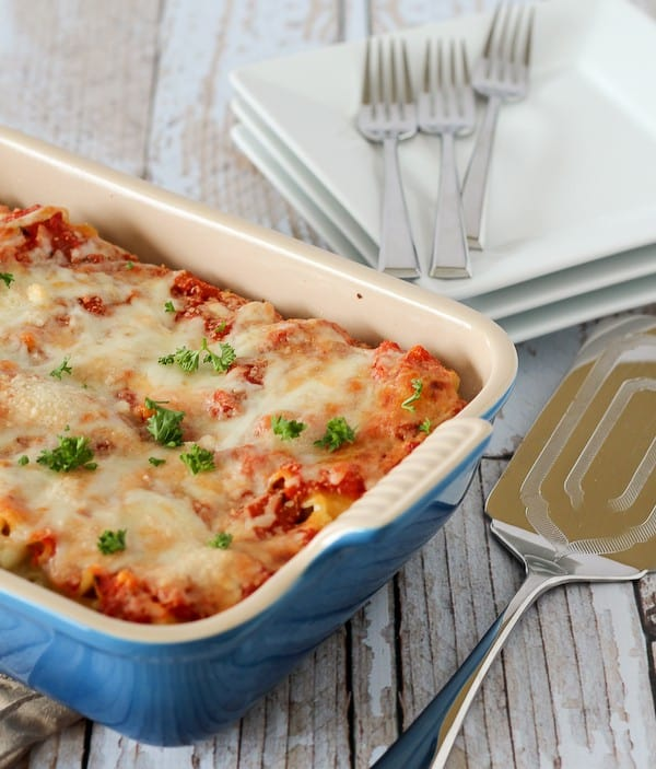 Blue glass baking dish full of pepperoni pizza lasagna rolls, covered in sauce and cheese, that have been baked so the cheese is melted. Fresh parsley is sprinkled on top.