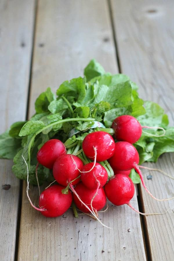 Fresh radishes in bunch, on wooden surface.