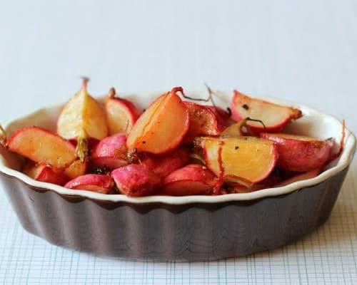 Shallow oval dish containing roasted radishes.