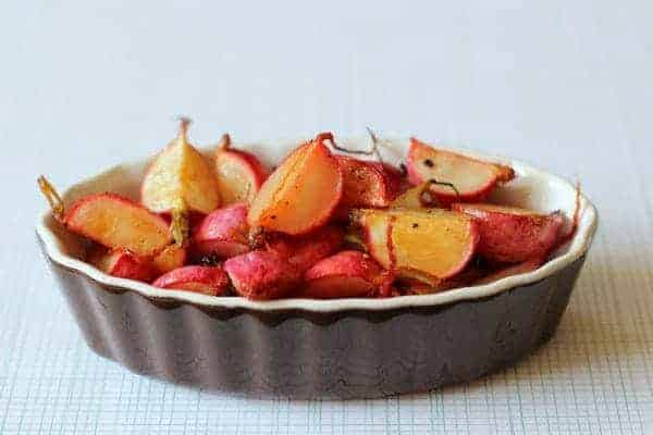 Shallow brown stoneware dish containing roasted radishes.