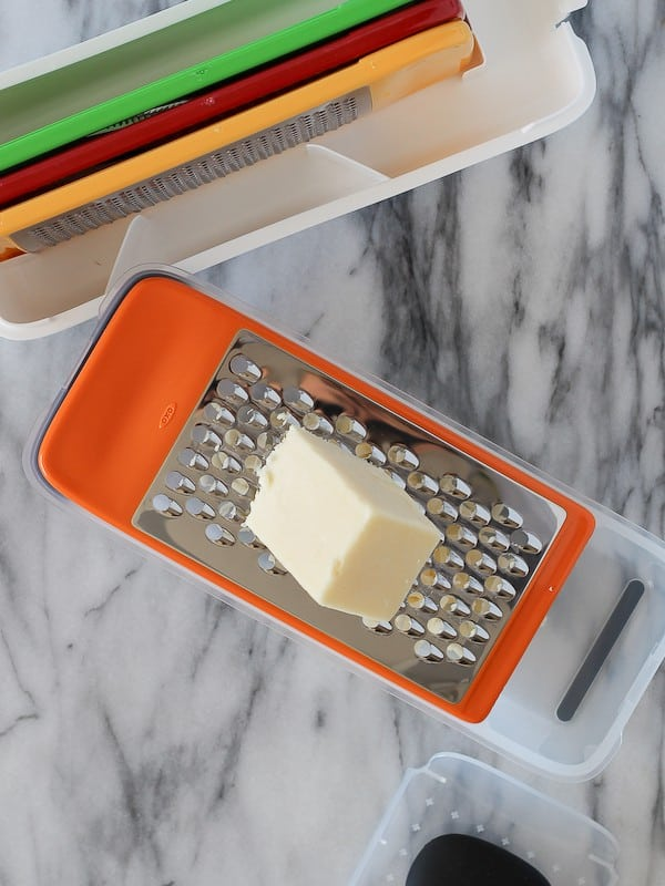 Overhead view of white cheddar cheese being grated on a box grater.