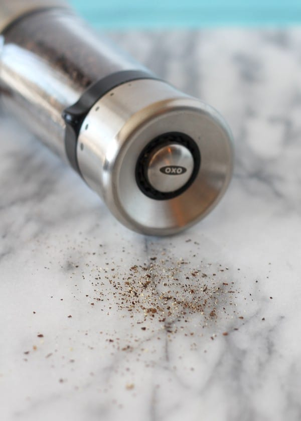 A pepper mill tipped over on a white and gray marble surface, pepper spilling out of it.