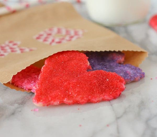 Decorated brown paper bag with Valentine's Day cookies spilling out onto white marble countertop.
