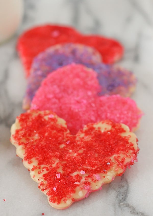 Heart-shaped cookies, red, pink, and purple, layered on white marble counter.