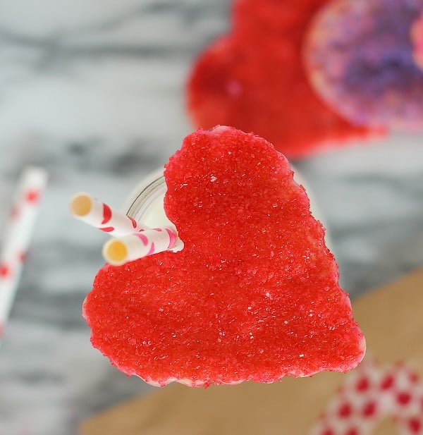 Overhead view of red heart cookie balanced on milk bottle with 2 striped straws.
