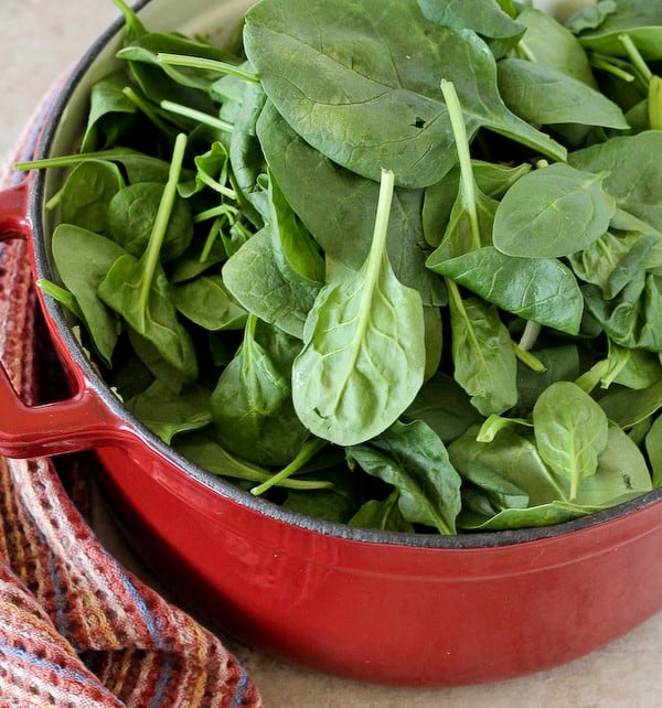 Dutch oven with fresh spinach leaves piled in.