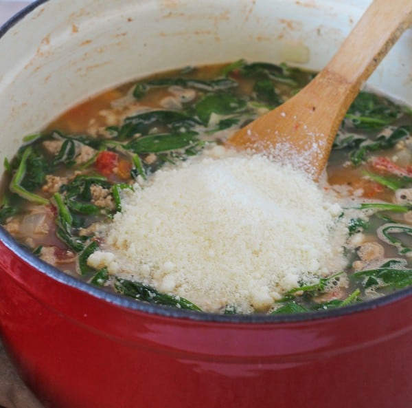 Closeup of Dutch oven containing soup, with parmesan cheese added on top.
