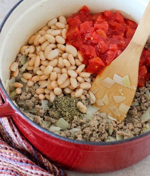 Overhead of Dutch oven containing ingredients for soup, before they are mixed together.