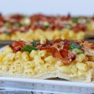 Slice of macaroni and cheese pizza on white plate.