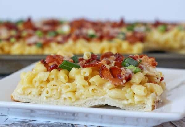 Square of macaroni and cheese pizza on white plate. Pizza in baking pan in background.
