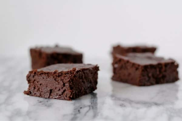 Front view of four brownies scattered on white marble surface.