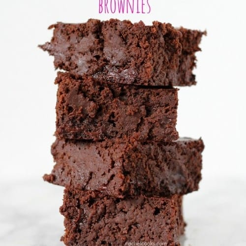 Four brownies stacked on white marble surface.