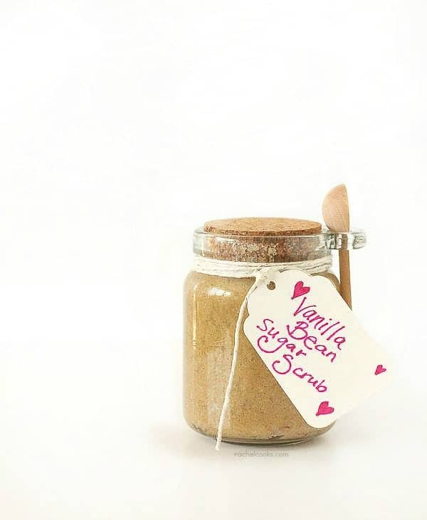 """Small clear jar, with cork stopper and wooden spoon attached, tied with white twine, and labelled """"Vanilla Bean Sugar Scrub""""."""