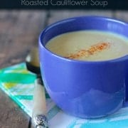 Blue ceramic mug containing cauliflower soup garnished with paprika.