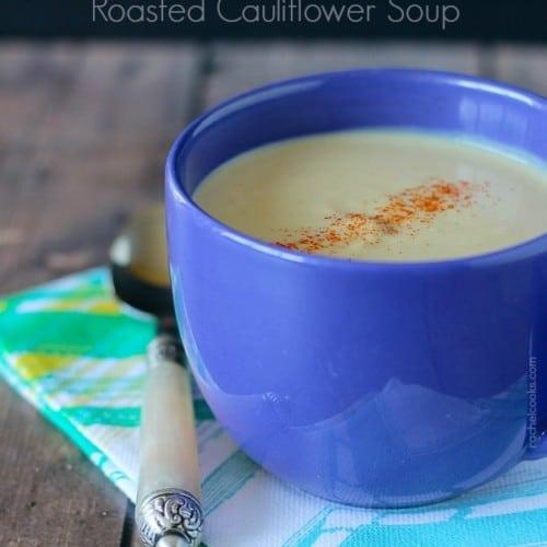 Blue ceramic mug containing cauliflower soup garnished with paprika.