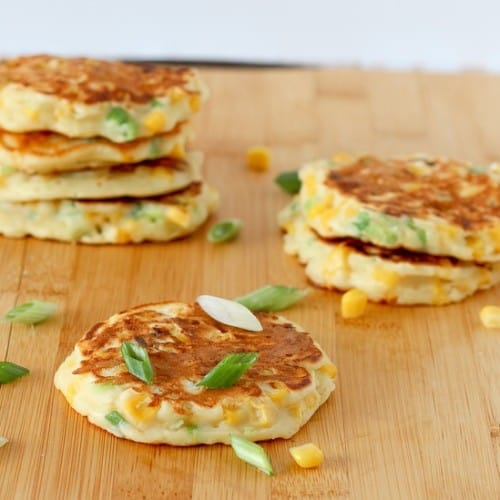 Several corn cakes on wooden cutting board, garnished with sliced green onions and corn kernels.