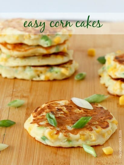 "Several corn cakes on wooden cutting board, with sliced green onions and corn kernels scattered between them. Text overlay reads ""easy corn cakes."""