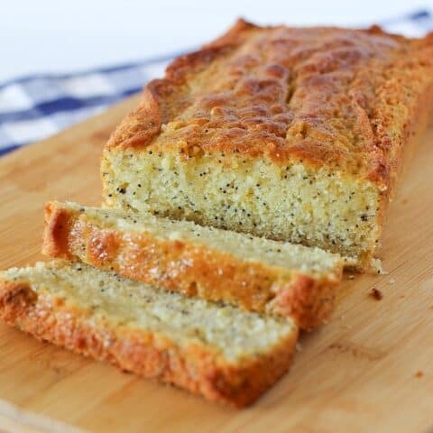 Image of a loaf of lemon poppy seed bread with two slices cut off.