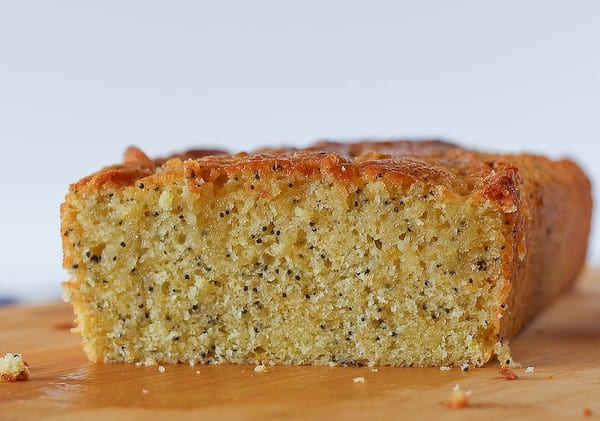 Image of a loaf of lemon poppy seed bread, shot straight on. It is placed on a wooden cutting board. Crumbs are scattered around.