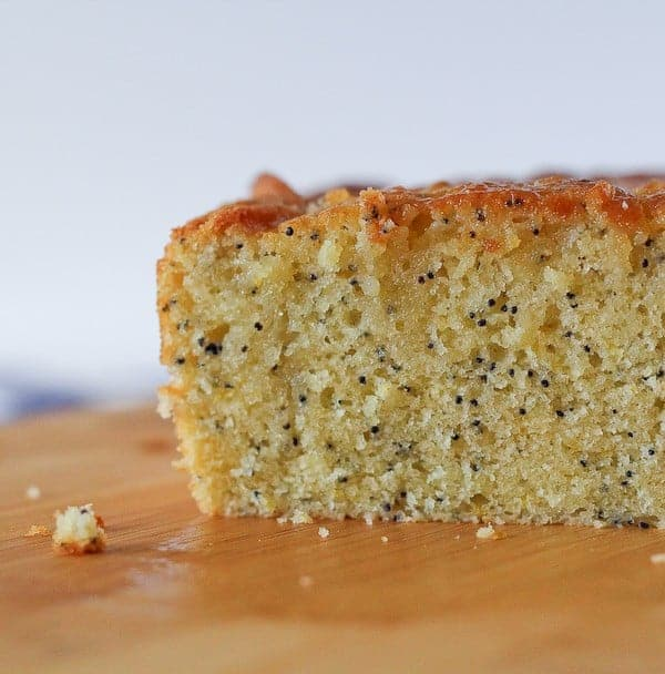 Close up Image of a loaf of lemon poppy seed bread. Crumbs are also scattered around.