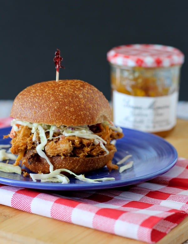 Image of a pulled pork sandwich on a whole wheat bun topped with shredded green cabbage slaw. It is held together with a red-topped toothpick and placed on a blue plate.