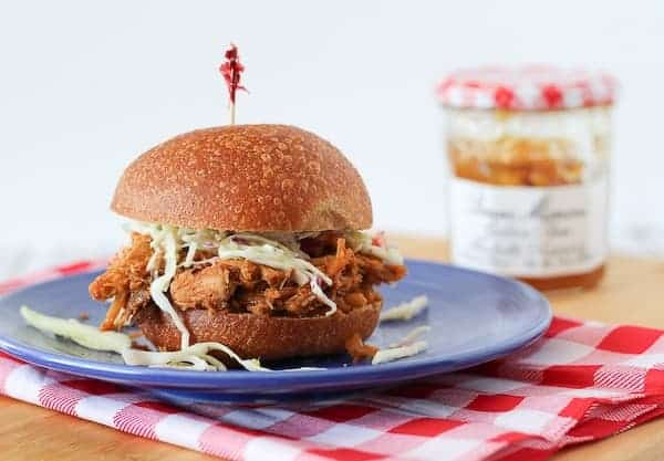 Horizontal image of a pulled pork sandwich on a blue plate with a red and white linen beneath it.
