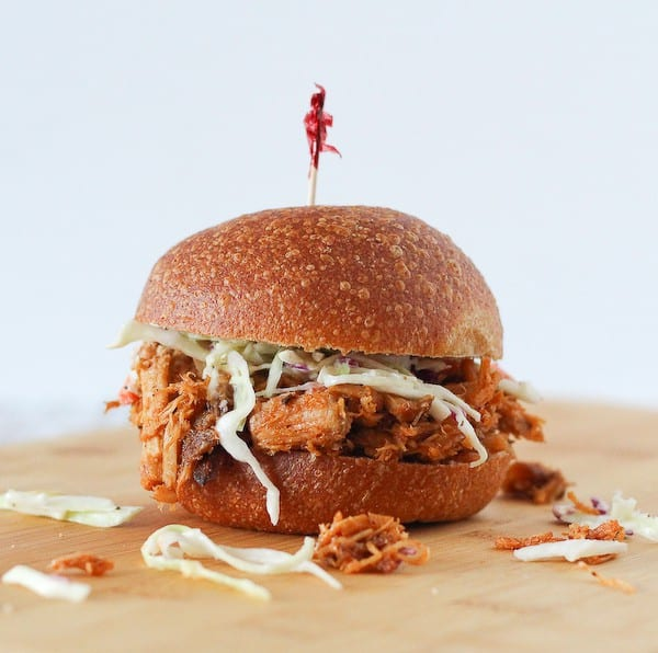 Image of a pulled pork sandwich on a wooden cutting board.