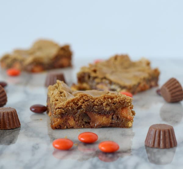 Scattered on marble countertop are blondies, Reese's pieces, and peanut butter cup minis.