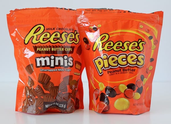 A bag of Reese's Minis and a bag of Reese's Pieces, side by side.