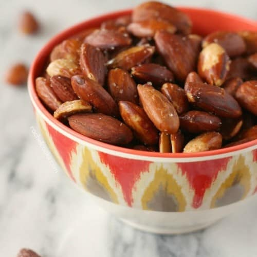 Roasted almonds in round decorative bowl on white marble surface.