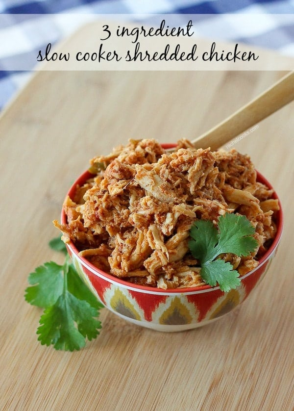 Image of slow cooker shredded chicken for tacos, in a bowl, garnished with sprigs of cilantro.