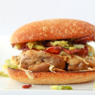 Chicken Burger with Bacon, Gouda and Leeks - close up image on a white background.