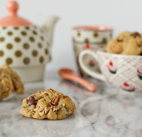 Arrangement of cookies, teapot, spoon, cups, on white marble surface.