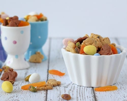 Easter snack mix in small white bowl, with multi colored egg cups in background.