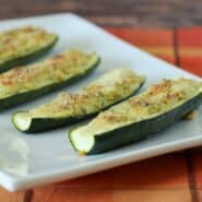 Partial image of white platter containing 4 cheese stuffed zucchini, on orange plaid cloth.