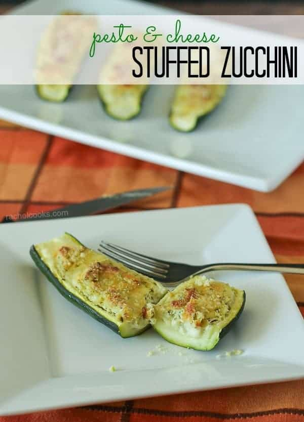 """Half zucchini stuffed with cheese, topped with panko, with bite cut off, on white plate with fork. Also in the image is text overlay, """"pesto & cheese stuffed zucchini""""."""