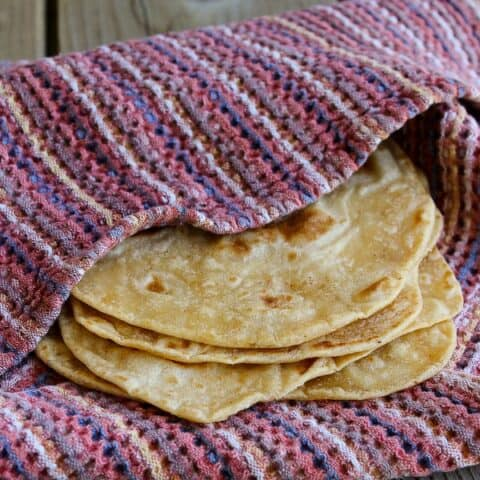 Closeup side view of 4 tortillas, partially wrapped in woven cloth.