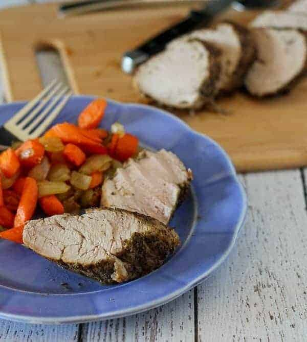 Image of pork tenderloin served on a blue plate with carrots and onions.