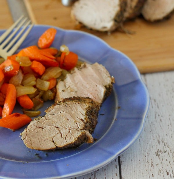 Image of two slices of cooked pork tenderloin on a blue plate served with carrots.