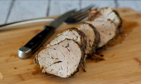 Horizontal image of cooked, sliced pork tenderloin on a cutting board with a knife.