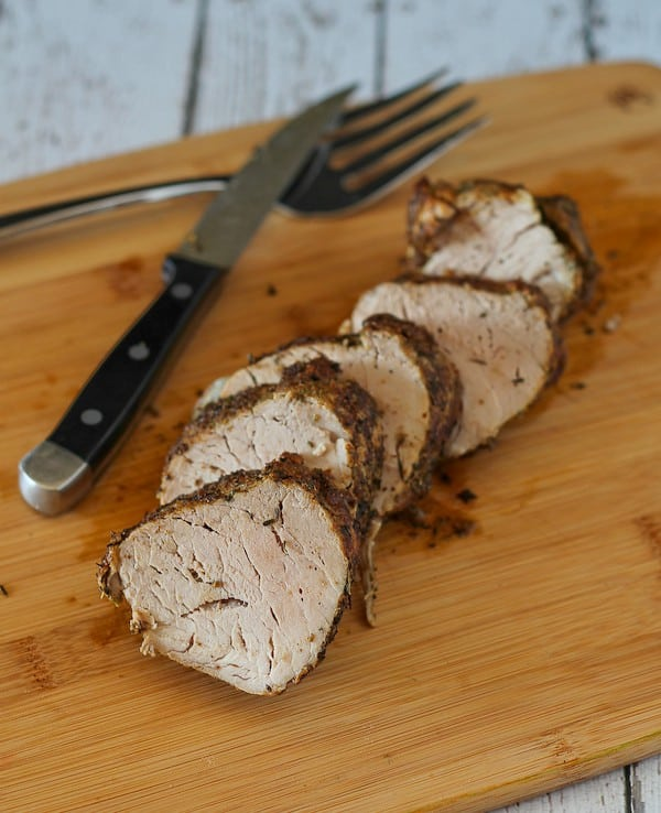 Image of sliced pork tenderloin on a cutting board with a fork and knife.