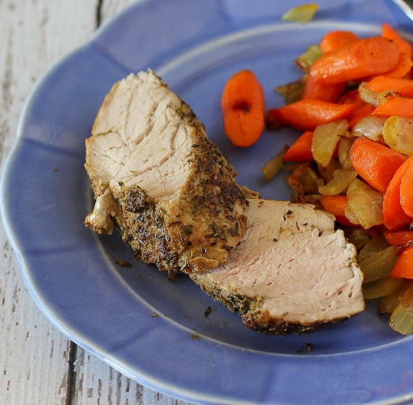 Close up image of two slices of pork tenderloin on a blue plate, served with roasted carrots and onions.