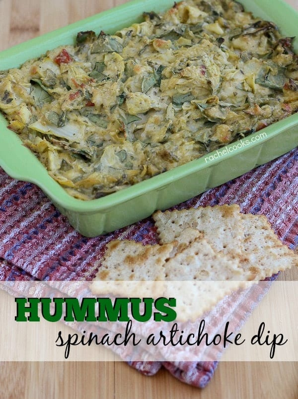 """Pale green rectangular casserole dish containing dip, on woven cloth, with crackers scattered. Text overlay reads """"Hummus spinach artichoke dip""""."""