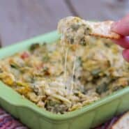 Front view of casserole dish containing artichoke dip with finger holding cracker loaded with dip.