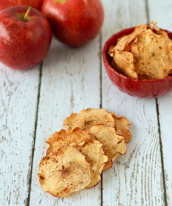 Several apple chips stacked on white board background, with red bowl containing more apple chips and a few apples in the background.