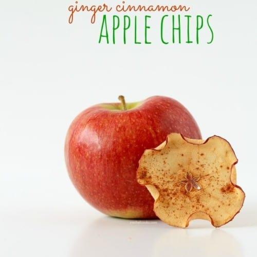 """One apple chip, propped on a red apple, with text overlay """"Ginger Cinnamon Apple Chips."""""""