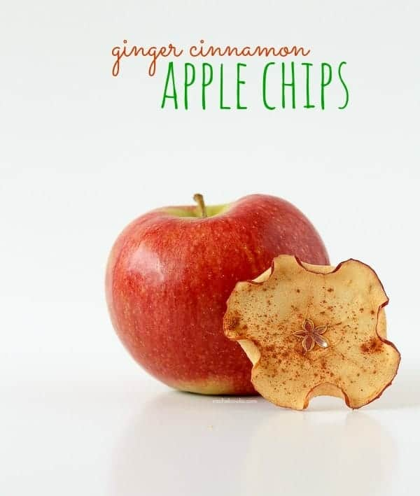 "One red apple, with an apple chip stacked against it, on a white background. Text overlay reads ""Ginger cinnamon apple chips."""