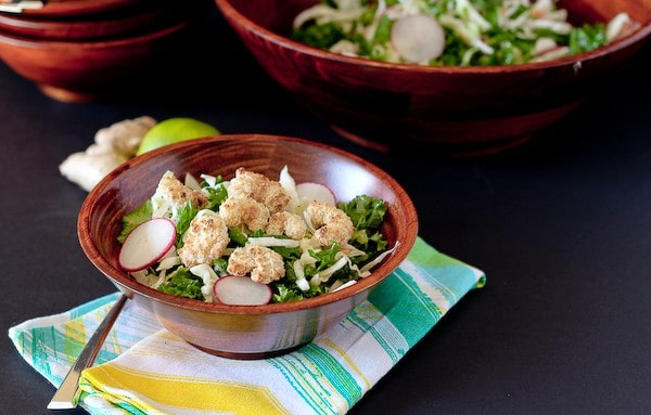 Kale salad with popcorn shrimp in wooden bowl, on folded cloth.