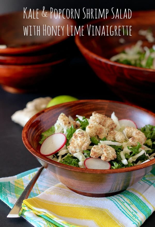 """Kale salad recipe in wooden salad bowl, on green and yellow striped cloth. Text overlay reads """"Kale & Popcorn shrimp salad with honey lime vinaigrette""""."""