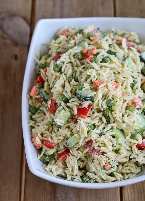 Large white bowl full of orzo, cucumbers, red bell peppers, carrots, and fresh dill.